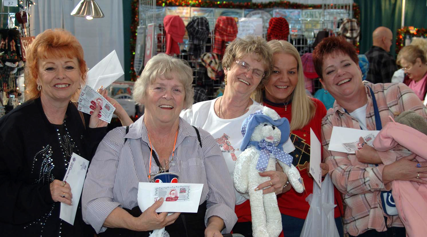 a group of ladies displaying holiday cheer at a previous christmas gift hobby show were awarded with merry money which serves as free money to use at any - Christmas Gift And Hobby Show